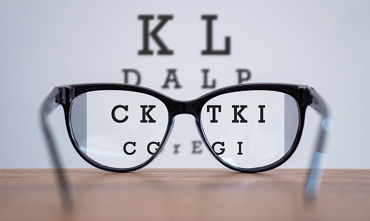 Eyeglasses during optometric examination concept with wooden table, Glasses on table and alphabet letter front view.