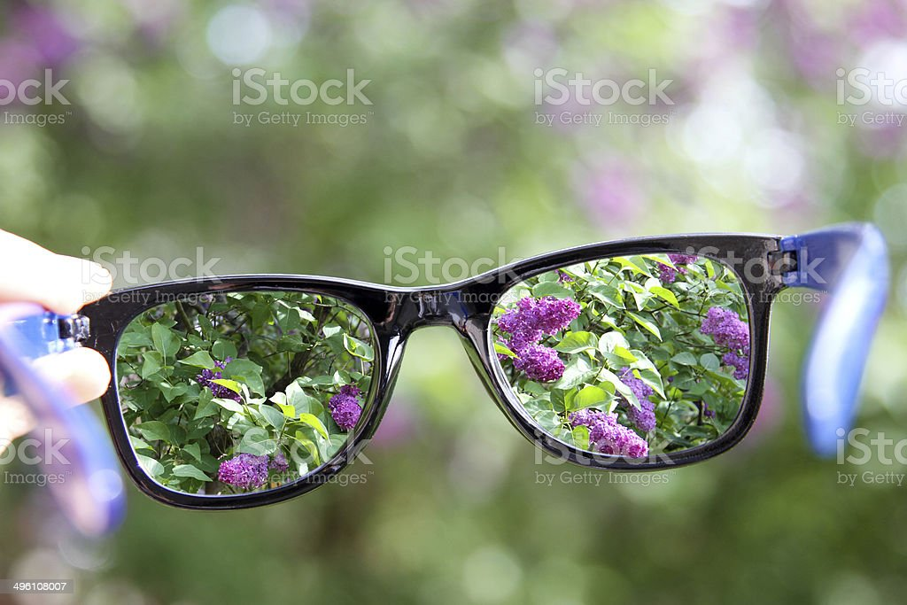eyeglasses in the hand over blurred background stock photo