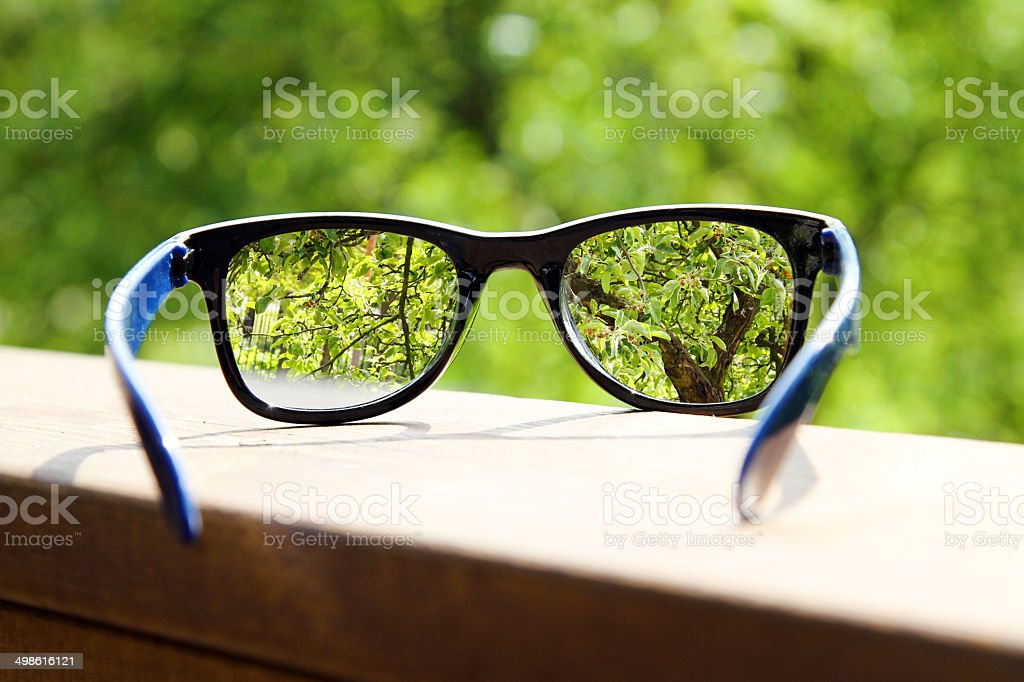 eyeglasses in the hand over blurred tree background stock photo
