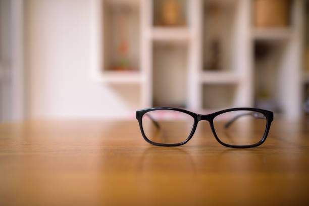 Eyeglasses laying on top of wooden table at home stock photo