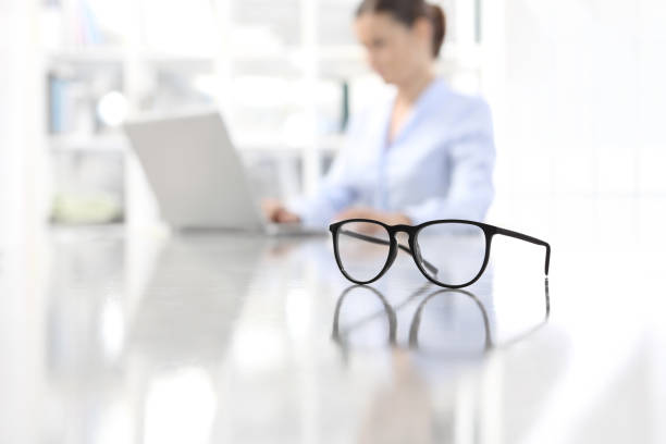 eyeglasses leaning on desk and woman working on computer at office in background - lens eye stock pictures, royalty-free photos & images