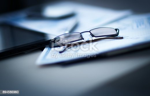 istock Eyeglasses lie on the documents and charts, next to the Tablet PC 894586960