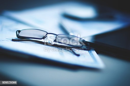 istock Eyeglasses lie on the documents and charts, next to the Tablet PC 939529366