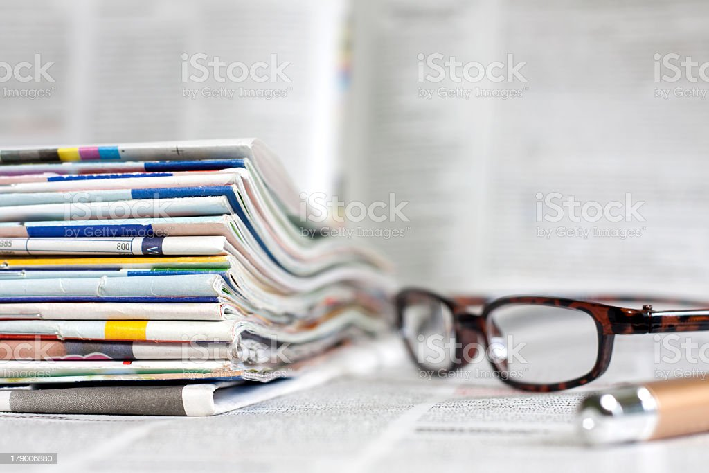Eyeglasses next to a stack of magazines on blurry background royalty-free stock photo