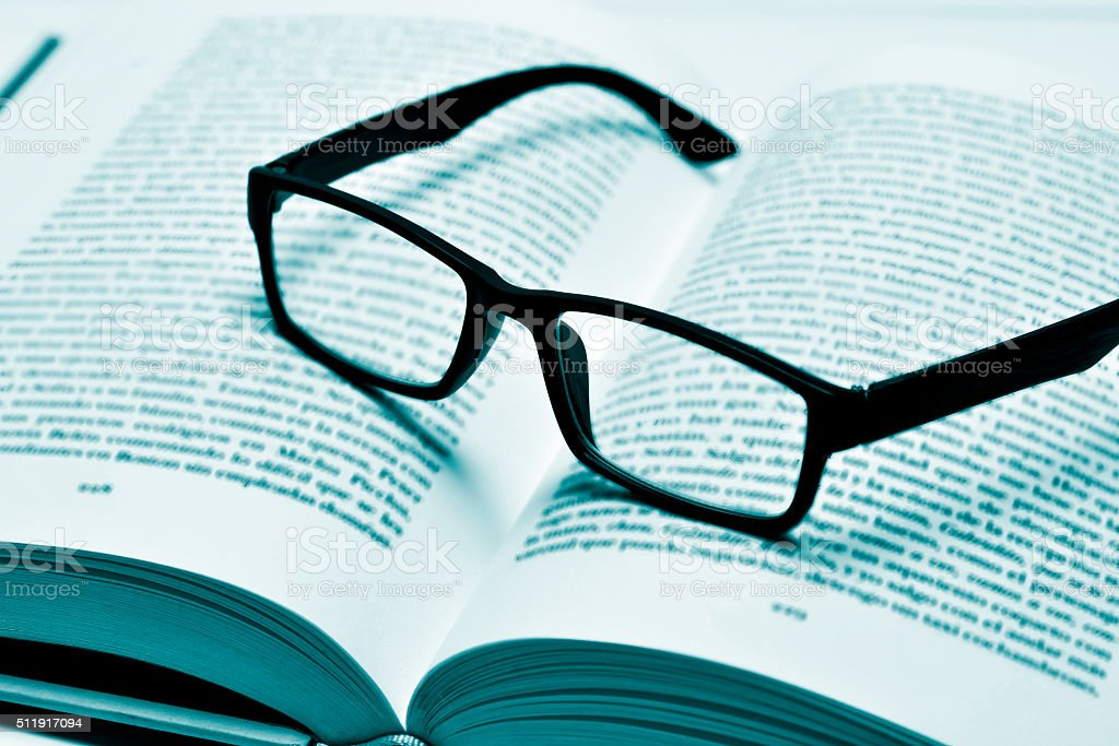 eyeglasses on an open book, in duotone stock photo