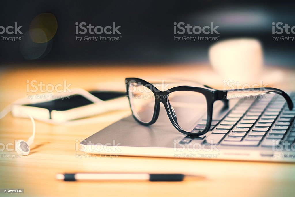 Eyeglasses on laptop keyboard with headphones and diary on woode stock photo