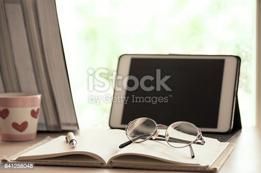 istock Eyeglasses on notebook with digital tablet in the workplace 641258048