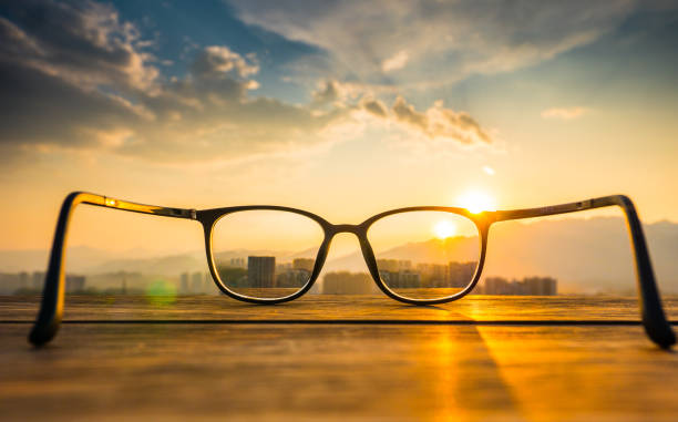 Eyeglasses on table with sunset stock photo