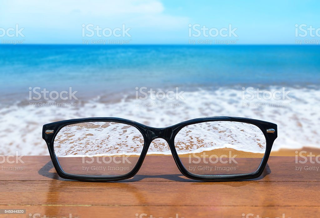 eyeglasses on wooden table front of the tropical sea stock photo