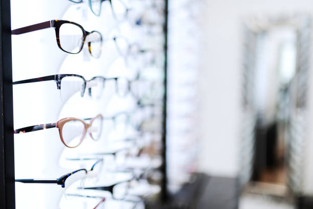eyeglasses sorted in line on shelf at optician. - optometrist stock pictures, royalty-free photos & images