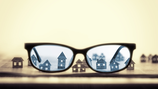 626187670 istock photo Eyeglasses  with paper houses 626187670