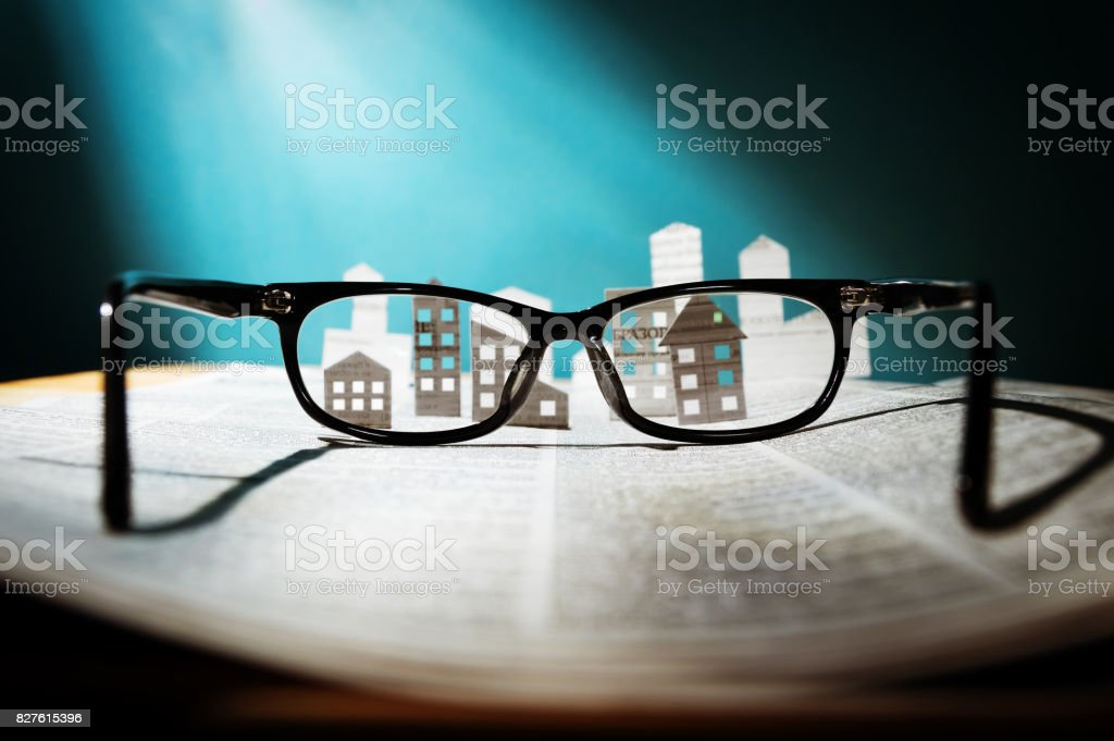 Eyeglasses  with paper houses. stock photo