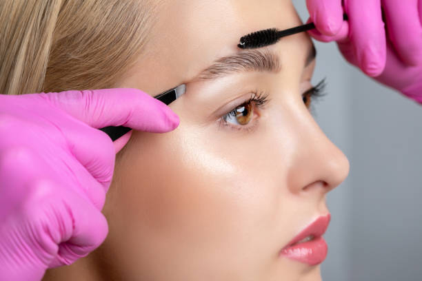 Eyelash artist plucks eyebrows with tweezers. Beautiful blonde woman having Permanent Make-up Tattoo on her Eyebrows. Professional makeup and cosmetology skin care. stock photo