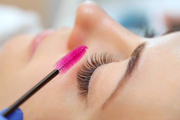 Eyelash extension procedure close up. Beautiful woman with long eyelashes in a beauty salon. Makeup concept stock photo