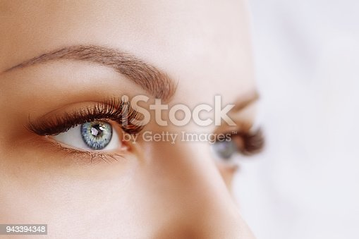 istock Eyelash Extension Procedure. Woman Eye with Long Eyelashes. Close up, selective focus 943394348