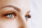Eyelash Extension Procedure. Woman Eye with Long Eyelashes. Close up, selective focus