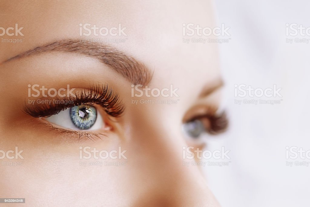 Eyelash Extension Procedure. Woman Eye with Long Eyelashes. Close up, selective focus – zdjęcie