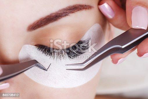 istock Eyelash Extension Procedure. Woman Eye with Long Eyelashes. Lashes, close up, macro, selective focus 845708412