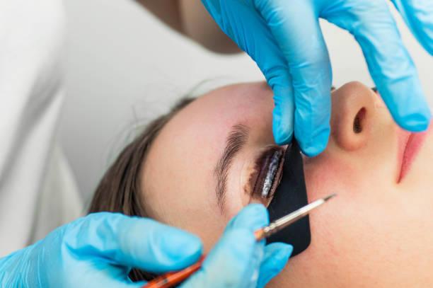 eyelash-laminierverfahren. färbung, curling, laminieren, wimpernaufzug. eyelash extension. verlängerung von wimpern für mädchen im schönheitssalon - dauerwelle stock-fotos und bilder