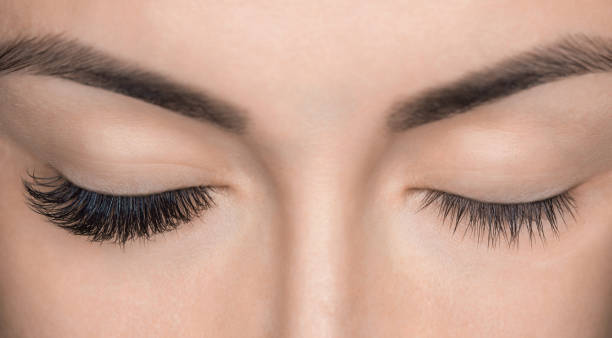 Eyelash removal procedure close up. Beautiful Woman with long lashes in a beauty salon. stock photo