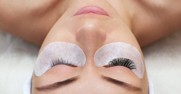 Eyelash removal procedure close up. Beautiful Woman with long lashes in a beauty salon. Eyelash removal procedure close up. Beautiful Woman with long lashes in a beauty salon. Eyelash extension. false eyelash stock pictures, royalty-free photos & images