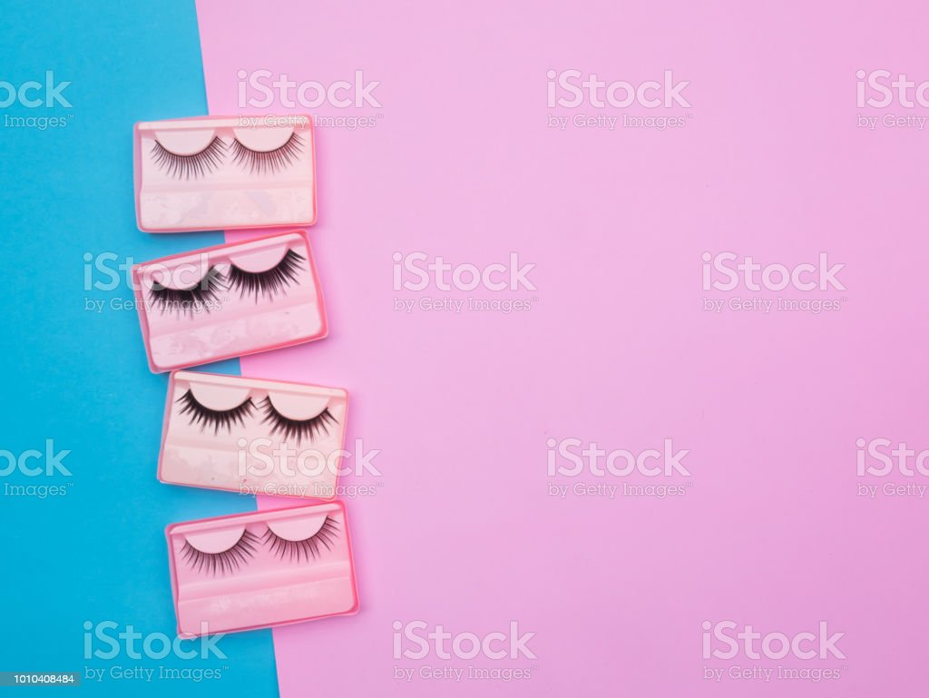 Eyelashes in the box on pink and blue backgorund stock photo
