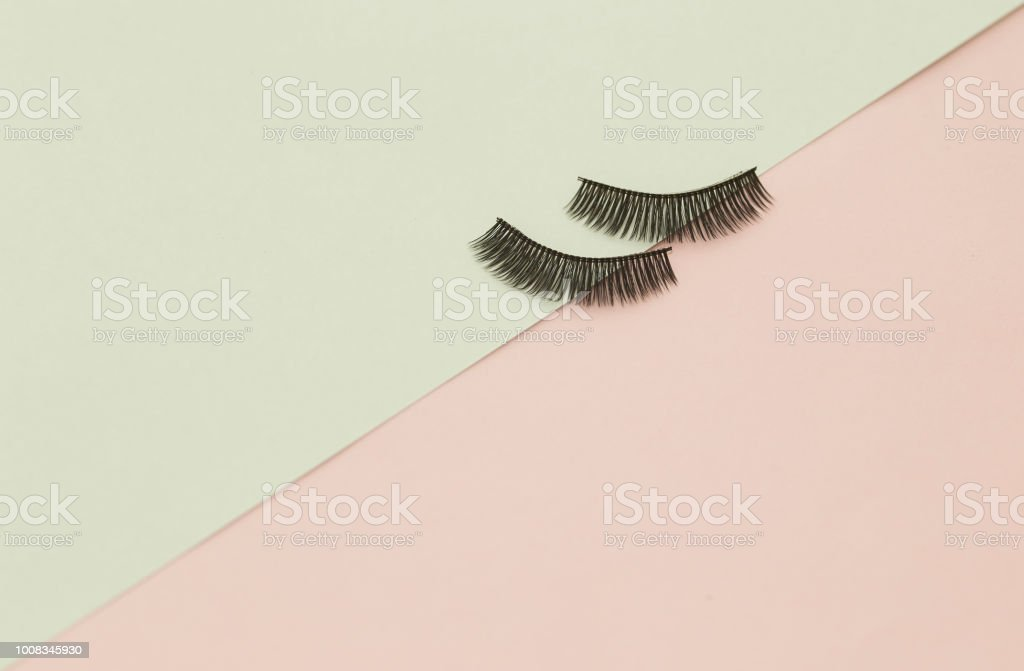 Eyelashes on pink and green paper backgorund stock photo