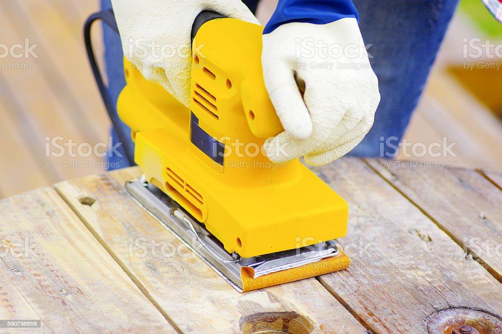 eyellow electric sander over a wood table Стоковые фото Стоковая фотография