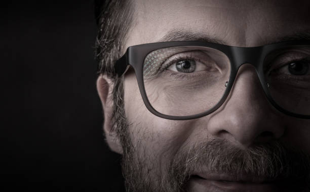 Eyes and glasses - man's face close up (macro) Eyes and glasses - happy smiling bearded caucasian man's face close up (macro). Successful businessman portrait on black background, dark moody light. Layout with free text (copy) space. close up stock pictures, royalty-free photos & images