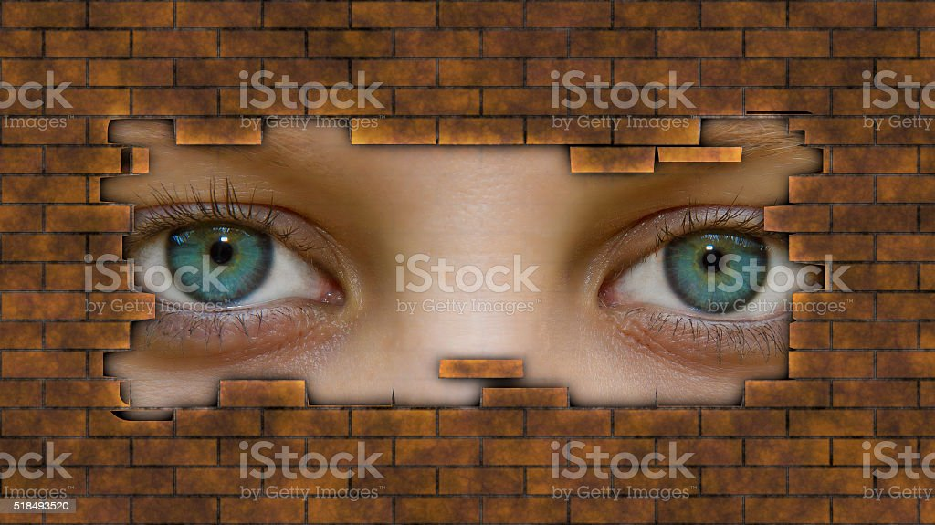 Eyes behind a wall stock photo
