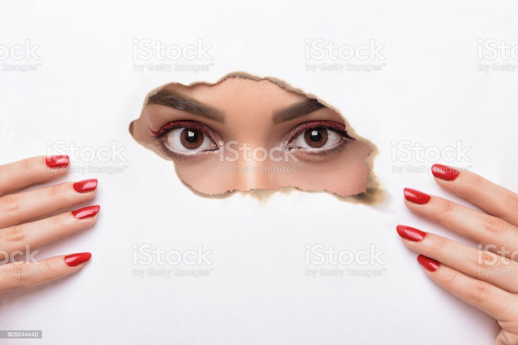 Eyes looking through the hole of wall. stock photo