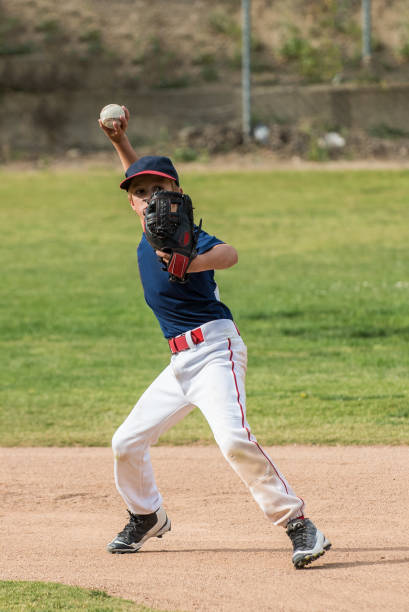 Eyes on target and ready to throw Little league short stop baseball player has arm loaded and ready to throw the ball across the diamond. all star stock pictures, royalty-free photos & images