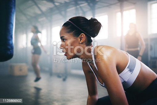 Cropped shot of a focused young sportswoman in the gym sitting down and taking a break