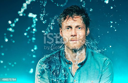Portrait of a man who wears a shirt. He gets a bucket full of water in the head, but do not close his eyes. His shirt, hair and face gets wet. Lots of small drops. The photo is shot hispeed. The background is dark blue.