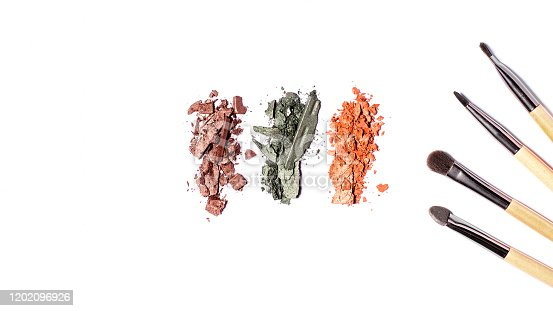 861986852 istock photo Eyeshadow palette in warm tones and makeup brushes of different sizes isolated on white background, top view, copy space. Crashed eyeshadow samples on white, beauty concept 1202096926