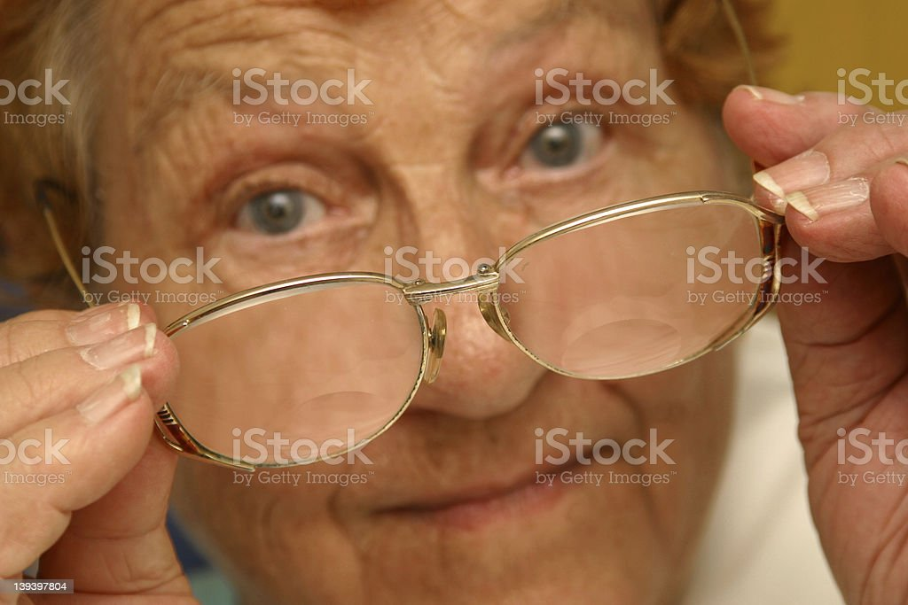 Eyesight Assitance Photo of a senior woman with her glasses held out. Adult Stock Photo