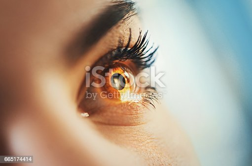 Macro shot of mid 20's brown eyed woman having her eyes examined at optometrists office. Her head is placed into tomography machine and light beam is shining through her retina and lens.