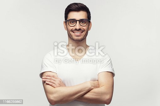 1045886560 istock photo Eyewear fashion. Portrait of handsome young man in casual white t-shirt and trendy eyeglasses, looking at camera, isolated on gray background 1166255862