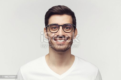 1045886560 istock photo Eyewear fashion. Portrait of smiling handsome young man in casual white t-shirt and trendy eyeglasses, looking at camera, isolated on gray background 1166255941