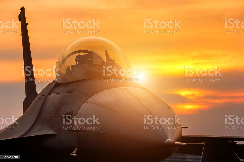 f16 falcon fighter jet parked on sunset background stock photo