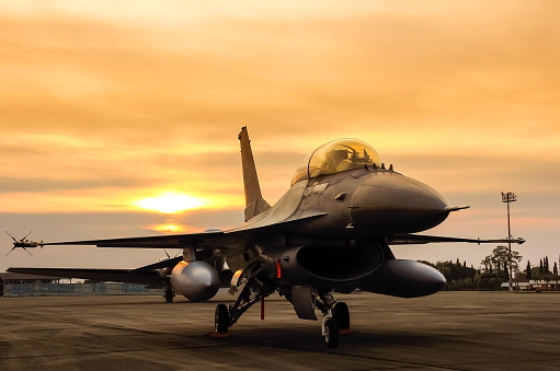 f16 falcon fighter jet in the base on sunset  background