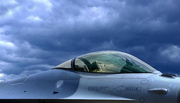 F-16-Fighting Falcon with clouds A F-16 fighter jet photographed from the side with gray clouds in the background f 16 fighting falcon stock pictures, royalty-free photos & images