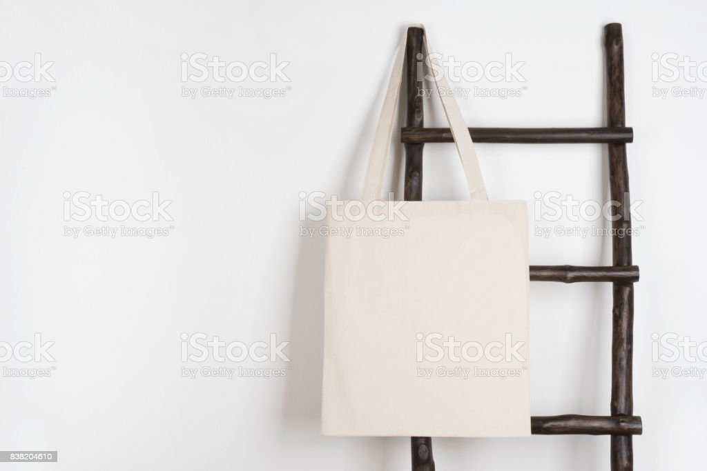 Fabric cloth shopping bag mockup hanging on vintage wooden stepladder stock photo