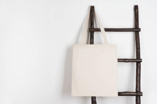 Maqueta de bolso de compras tejido paño colgando en escalera madera vintage - foto de stock
