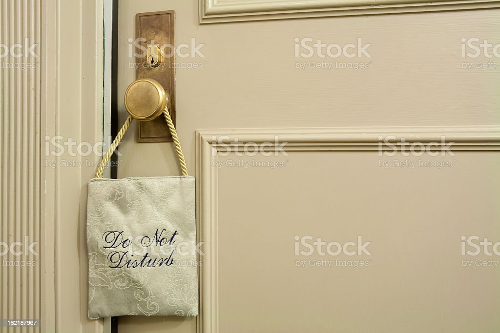 A fabric 'do not disturb' sign hanging on a cream door stock photo