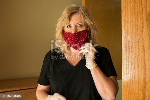 Blond female healthcare worker adjusts her fabric face mask in a patient's room during the corona virus COVID-19 pandemic during a shortage of medical face masks
