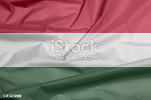 istock Fabric flag of Hungary. Crease of Hungarian flag background. 1051003338