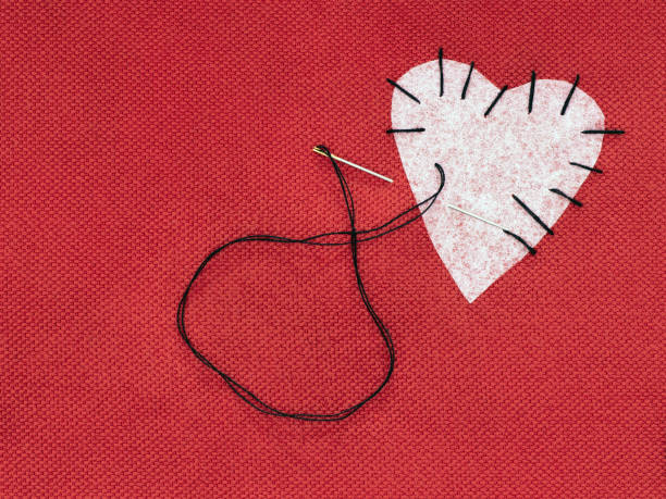 Fabric heart red with white patch and black sewing thread. Mend broken heart concept. Fabric heart red with white patch and black sewing thread. Mend that broken heart concept. red broken heart sewn threads stock pictures, royalty-free photos & images