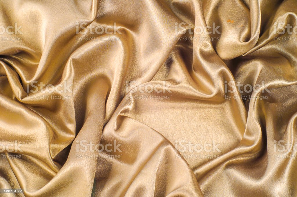 Fabric made of silk fabric metal thread metallic sheen gold. Just like looking at a stunning waterfall, this golden yellow Silk Charmeuse stands alone. Luminous and light-flowing steel metallic color stock photo