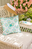 Fabric pillow, needle, thread and buttons sewing notions on chair in garden. Spring and summer home decorating crafts projects.